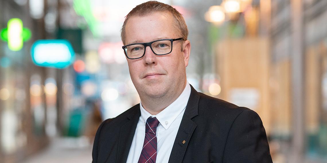 Porträtt av Martin Gunnarsson  i gatumiljö med suddig bakgrund.